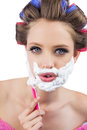 Young model in hair curlers posing with razor close up Royalty Free Stock Image