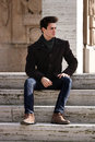 Young model man sitting on marble steps a the boy wearing a winter coat scarf blue jeans and ankle boots the day is sunny location Royalty Free Stock Photo