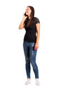 Young modern casual woman talking on the mobile phone full body length isolated over white Stock Photography