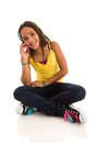 Young modern female talking on cellular teenage girl sitting floor cross legged cellphone isolated white background Stock Image