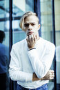 Young modern hipster guy at new building university blond fashion hairstyle having fun, lifestyle people concept Royalty Free Stock Photo