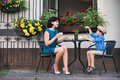 Young mom having coffee with her son in street cafe Royalty Free Stock Images