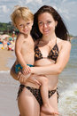Young mom holding little son in hands on the beach Royalty Free Stock Photos