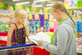 Young mother and adorable daughter in shopping cart select kids
