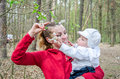 Young mother with baby daughter gives her daughter to smell the spring flowers on a tree Royalty Free Stock Photo