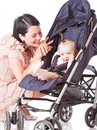 Young mother with baby in perambulator Stock Photos