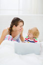 Young mother and baby playing with laptop in bed Royalty Free Stock Photo