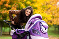 Young mother with baby in stroller walks in park Stock Photo