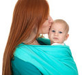 Young mother carrying baby boy sitting in sling Royalty Free Stock Photography