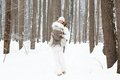 Young mother carrying her baby in forest on snowy day the a very Stock Photos