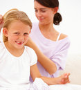 Young mother combing hair of her happy daughter Royalty Free Stock Photos
