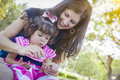 Young mother and cute baby girl applying fingernail polish mixed race in the park Stock Photography