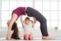 Young mother and daughter doing yoga exercise Royalty Free Stock Photo