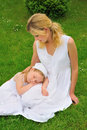Young mother and daughter resting in meadow Royalty Free Stock Photos