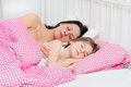 Young mother and daughter sleep in the morning in bed Royalty Free Stock Photography