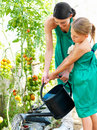 Young mother with daughter watering plant Stock Image