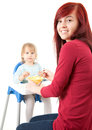 Young mother feeding hungry baby in highchair Stock Photography