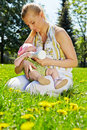 Young mother feeds her baby bottle sitting grass spring park Royalty Free Stock Photography