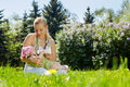 Young mother feeds her baby milk bottle sitting grass spring park Royalty Free Stock Photo