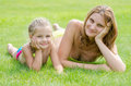 Young mother and five year old daughter lying on green grass and looking to frame