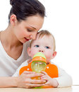 Young mother giving drink to baby from feeding cup Royalty Free Stock Photo