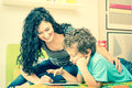 Young mother having fun learning with son using tablet on bed Royalty Free Stock Photo
