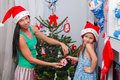 Young mother and her adorable little girl in santa claus hats decorate their christmas tree this image has attached release Royalty Free Stock Image