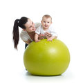 Young mother and her baby child doing yoga exercises on gymnastic ball isolated over white Royalty Free Stock Photo