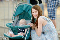 Young mother and her baby in a stroller smiling Stock Image