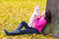 Young mother with her cute baby in autumn park beautiful and adorable daughter playing an Royalty Free Stock Photo