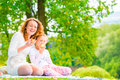 Young mother and her daughter eating apples in the park Royalty Free Stock Photo