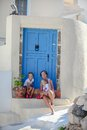 Young mother and her daughter sitting on doorstep of old house street of emporio santorini this image has attached release Stock Photography