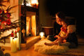 Young mother and her daughters by a fireplace on christmas Royalty Free Stock Photos