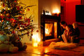 Young mother and her daughters by a fireplace on christmas Stock Photos