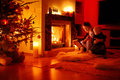 Young mother and her daughters using a tablet pc by fireplace Royalty Free Stock Image