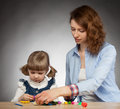 Young mother and her dauther modelling with plasticine dark background Stock Photo
