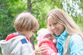 Young mother with her kids in the park forest son is jealous mum of younger sister Royalty Free Stock Photos