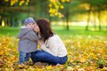 Young mother with her little baby boy having fun in the autumn park Stock Photo