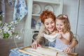 Young mother with her little daughter sculpt a dough portrait of on kitchen their noses is dirty at flour Royalty Free Stock Photo
