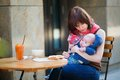 Young mother with her little son having breakfast in a cafe Royalty Free Stock Images