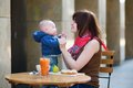 Young mother with her little son having breakfast in a cafe Stock Photo