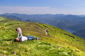 Young mother and her newborn baby relaxing high in mountains the with a stunning view over a lake Royalty Free Stock Photography
