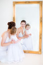 Young mother and her toddler daughter next mirr adorable in a white dress a big mirror Royalty Free Stock Images