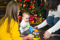 Young mother and her two children opening a Christmas presents b Royalty Free Stock Photo