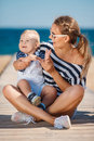 Young mother and her young son on the beach happy family relaxing near sea with little are dressed in striped t shirts white Stock Images
