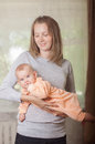 Young mother holding a baby at home Royalty Free Stock Photo