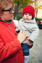 A young mother holding her cute baby girl wearing warm clothes Royalty Free Stock Images