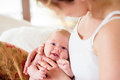 Young mother holding her newborn baby son home bedroom cute Royalty Free Stock Image