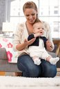 Young mother holding little baby girl on lap daughter kneeling on floor smiling Royalty Free Stock Photography