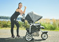 Young mother jogging with a baby buggy Royalty Free Stock Photo